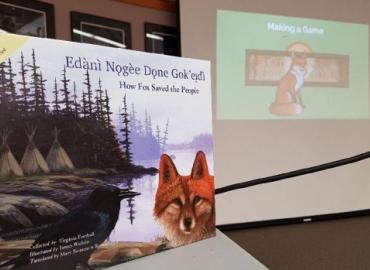 A photo of the book How Fox Saved the People in front of a slide presentation on the related video game