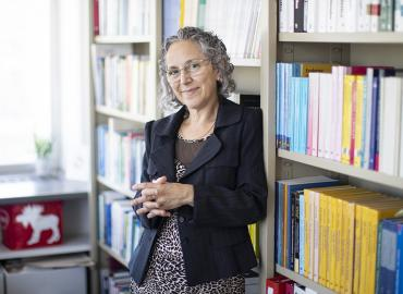 Photo of Sali Tagliamonte in front of book cases in her department office